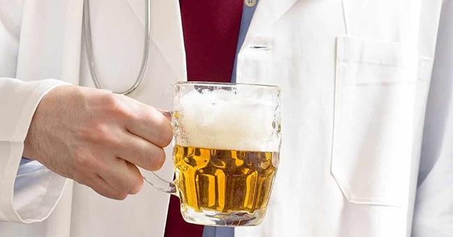 Врач с бокалом пива для лечения кашля