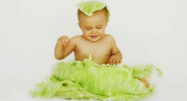 Ребенок и свежие листья капусты