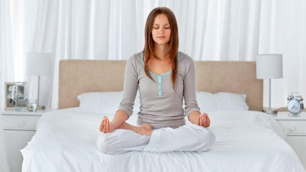 Медитация девушки на кровати