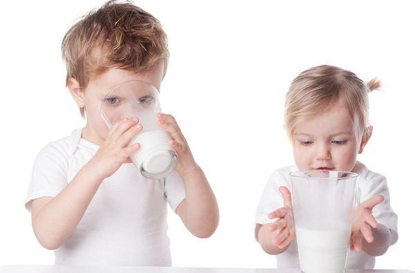 Мальчик и девочка пьют молоко с содой при кашле