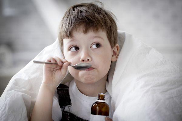 Мальчик пьет сироп от кашля